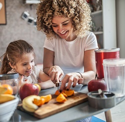 Lady cutting fruit with her daughter in her kitchen